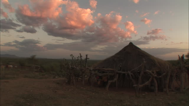 long shot static - rosy clouds gather over a grass hut in ethiopia / ethiopia - äthiopien stock-videos und b-roll-filmmaterial