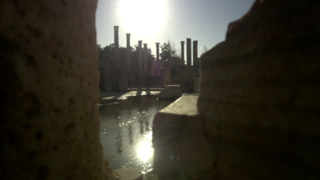 Long Shot static - Sunlight sparkles on a canal that flows past ruinous columns and buildings.