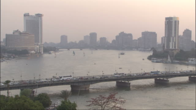 long shot, static - traffic crosses a bridge in cairo / egypt - river nile stock videos & royalty-free footage