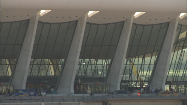 long shot static - travelers walk in front of the terminal at dulles international airport in dulles, virginia. / dulles, virginia, usa - dulles international airport stock videos and b-roll footage