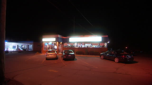 Long Shot static - Vehicles park in front of a diner.