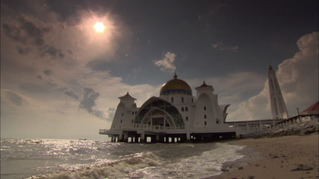 long shot static - waves wash up on a beach near a white church. / malaysia - pavilion video stock e b–roll