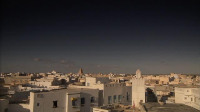 Long Shot static - White buildings surround a courtyard. / Libya