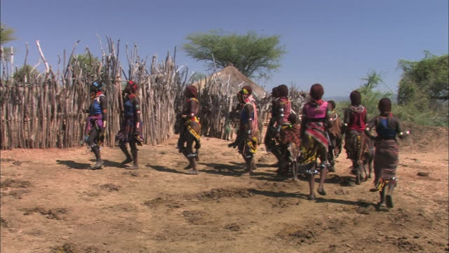 Long Shot static - Women and children dance about in an African village. / Ethiopia
