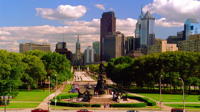 Long shot statue in park of Benjamin Franklin Parkway with skyscrapers in background / Philadelphia, Pennsylvania