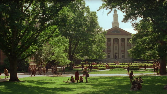 long shot students walking and socializing on campus of college or university / campus building (manning hall) in background / university of north carolina - university student stock videos & royalty-free footage