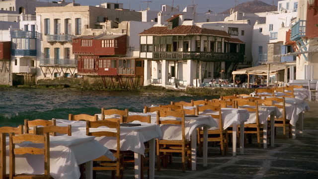 long shot tablecloths on tables flapping in the wind at outdoor cafe with water in background / mykonos, greece - mykonos stock videos & royalty-free footage