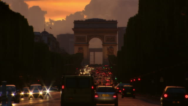 long shot the arc de triomphe and traffic on the champs-elysees at sunset - avenue des champs elysees stock videos & royalty-free footage