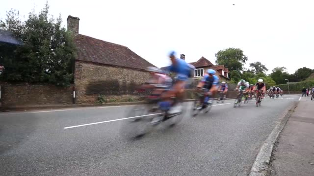 long shot the leading group of riders pass through the small village of compton during stage seven of the tour of britain from epsom racecourse to... - tour of britain stock videos & royalty-free footage