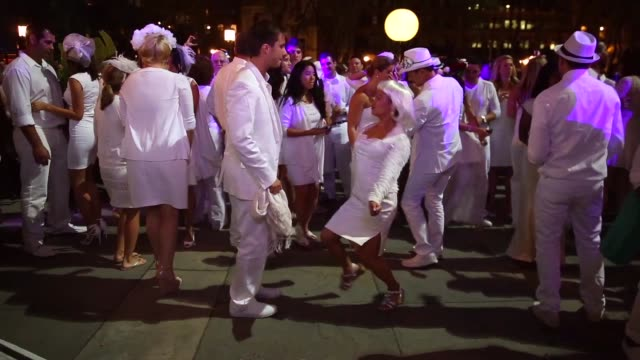 vídeos y material grabado en eventos de stock de long shot thousands of people all dressed in white set up picnic tables for the diner en blanc event on september 18 2013 in new york city some 4000... - silla plegable