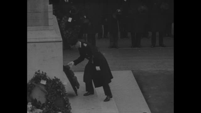 long shot tilt down armistice day ceremony at the cenotaph people wearing church cassocks walk toward the cenotaph soldiers stand at attention / pan... - 退位点の映像素材/bロール