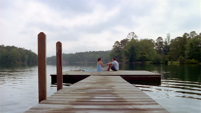 long shot tilt down couple sitting at end of dock on lake and talking - clarkesville stock videos & royalty-free footage