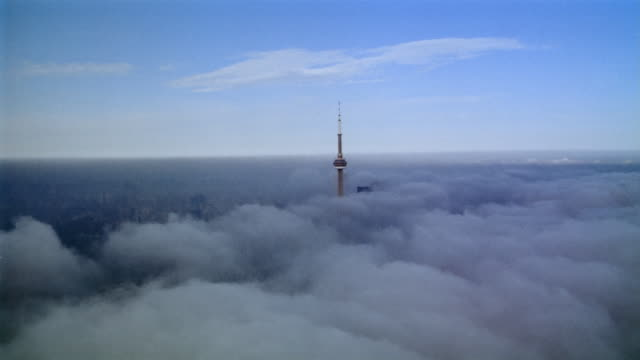 Long shot tilt up airplane point of view flying over clouds towards CN Tower / Toronto, Ontario, Canada