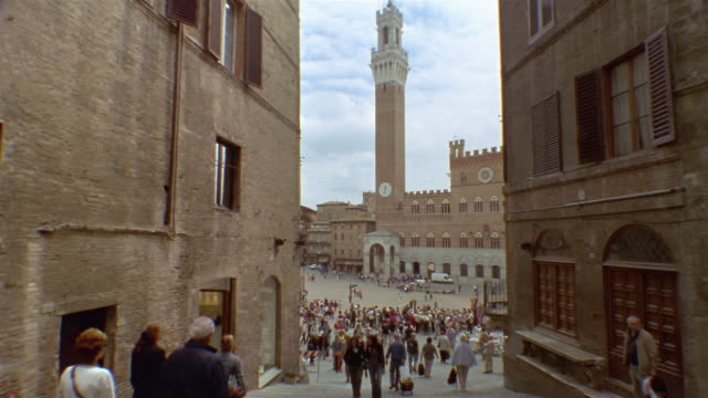 long shot tilt up people in the piazza del campo with palazzo pubblico and torre del mangia in background / siena, italy - palazzo pubblico stock videos and b-roll footage