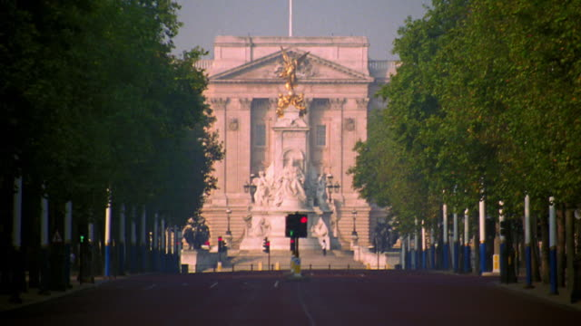 vídeos de stock, filmes e b-roll de long shot tilt up tilt down zoom out zoom in buckingham palace with queen victoria monument in foreground / london, england - palácio de buckingham