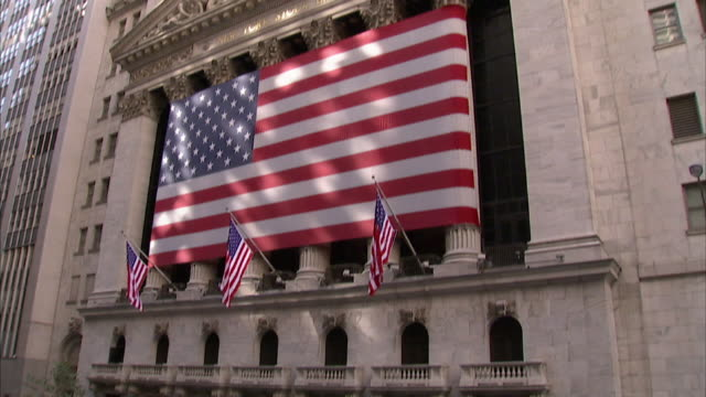 long shot tilt-down - a crowd gathers on wall street across from a large american flag on the new york stock exchange. / new york city, new york, usa - new york stock exchange stock videos & royalty-free footage