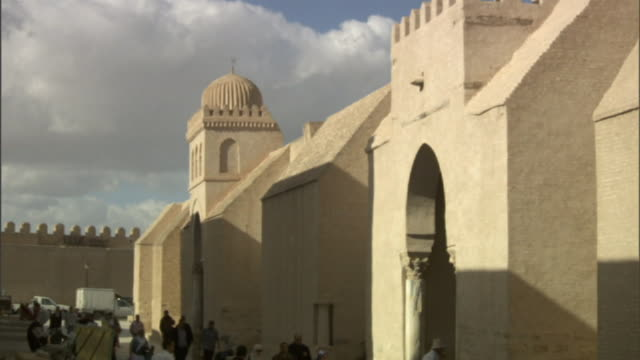 Long Shot tilt-down - Pedestrians pass a marketplace in a domed, arched courtyard in Libya. / Libya
