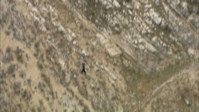 vídeos y material grabado en eventos de stock de long shot tilt-down tilt-up - a bungee jumper leaps from a bridge into a gorge / italy - puenting