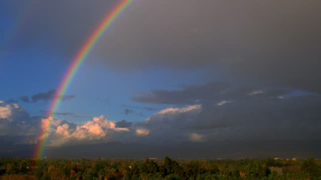 vídeos de stock, filmes e b-roll de long shot time lapse clouds moving behind rainbow over valley - arco íris