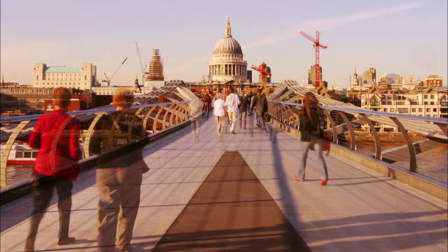Long shot time lapse pedestrians crossing the Millenium Bridge / London