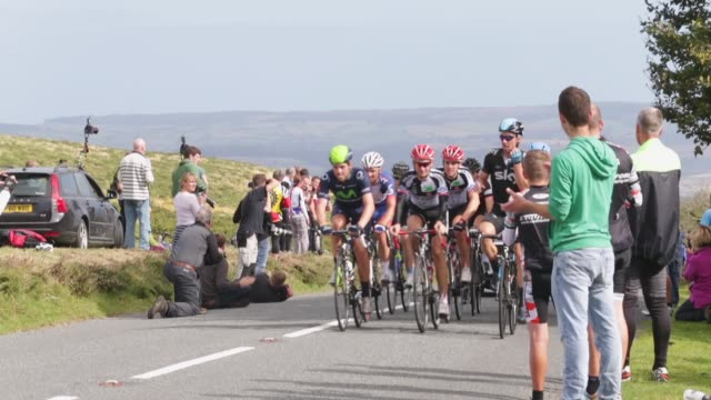 long shot tour of britain cyclists passing cheering fans stage six of the tour of britain made history this year as it was the first stage to host a... - tour of britain stock videos & royalty-free footage