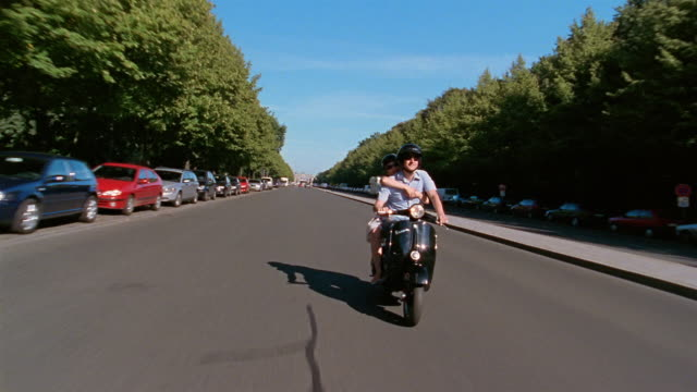 long shot tracking shot man and woman riding vespa down street / berlin, germany - motorino video stock e b–roll