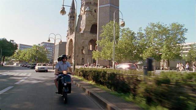 Long shot tracking shot man and woman riding Vespa past Kaiser Wilhelm Memorial Church / Berlin, Germany