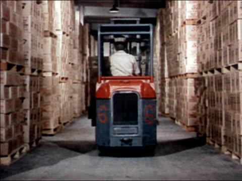 vidéos et rushes de 1951 long shot tracking shot man driving forklift carrying boxes of heinz 57 tomato ketchup along aisle of warehouse / audio - objet manufacturé
