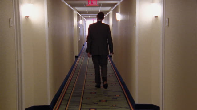 Long shot tracking shot man walking down hotel hallway / opening and closing door