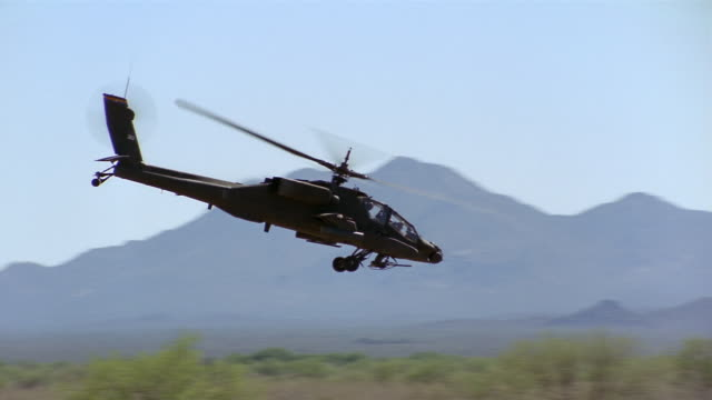 long shot tracking shot side view of apache helicopter flying low over field / mountains in background / california - アパッチヘリコプター点の映像素材/bロール