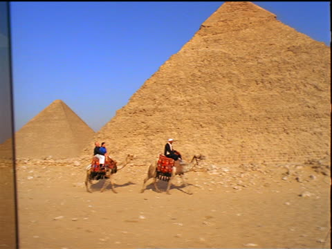 long shot tracking shot tourist couple riding camel behind guide on camel past great pyramids / giza, egypt - camel stock videos & royalty-free footage
