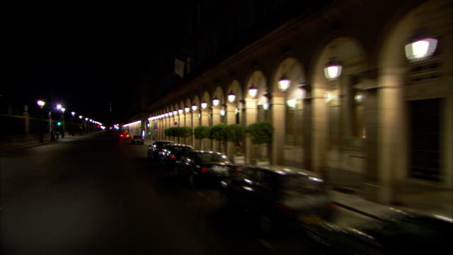 long shot tracking-left - cars line the shoulder of a road. / paris, france - arco architettura video stock e b–roll