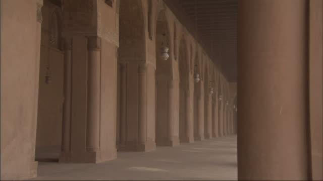 vídeos y material grabado en eventos de stock de long shot, tracking-left - lamps sway between columns at the mosque of ibn tulun / egypt - pórtico