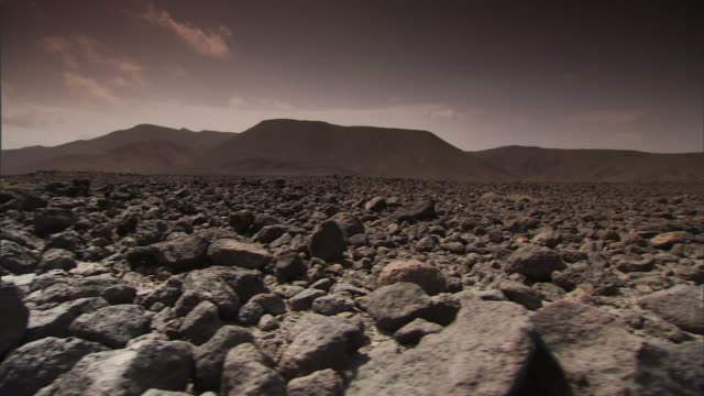 vidéos et rushes de long shot tracking-left - volcanic rock covers a vast lava field. / djibouti - roc