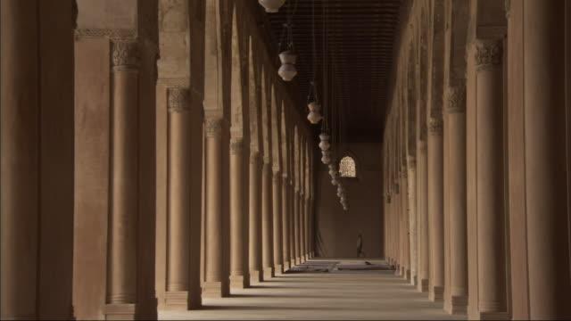 vídeos y material grabado en eventos de stock de long shot, tracking-right - lamps sway between columns at the mosque of ibn tulun / egypt - pórtico