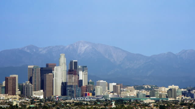 long shot tracking-right - the pacific ocean rises above the los angeles skyline and san gabriel mountain in a computer-generated animation. / los angeles, california, usa - etablera scenen bildbanksvideor och videomaterial från bakom kulisserna