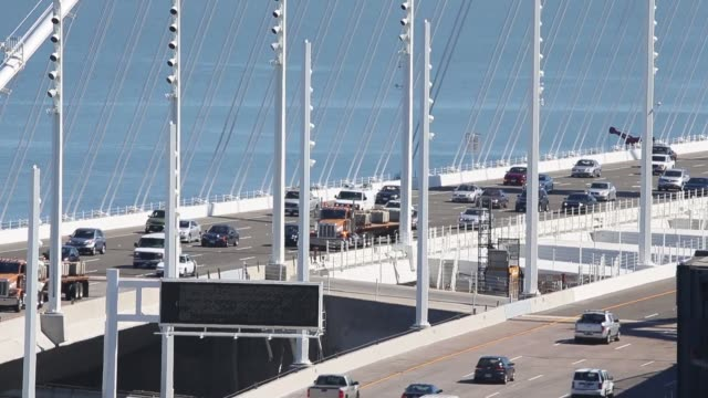 vídeos de stock e filmes b-roll de long shot traffic flows across the new eastern span of the san francisco oakland bay bridge as the old eastern span sits empty on the morning after... - san francisco oakland bay bridge