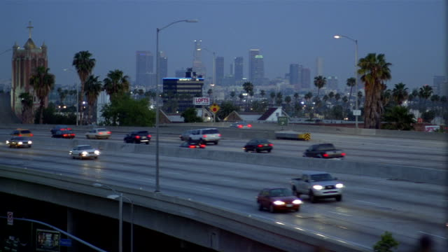 Long shot traffic on elevated freeway at dusk / view of downtown skyline / Los Angeles, California