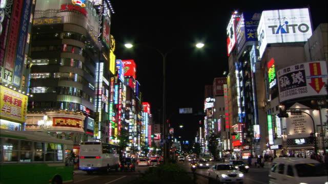 long shot traffic on neon-lit shinjuku street at night / tokyo, japan - 2005年点の映像素材/bロール