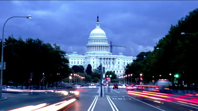 Long shot traffic on Pennsylvania Avenue in evening with view of US Capitol / Washington, DC