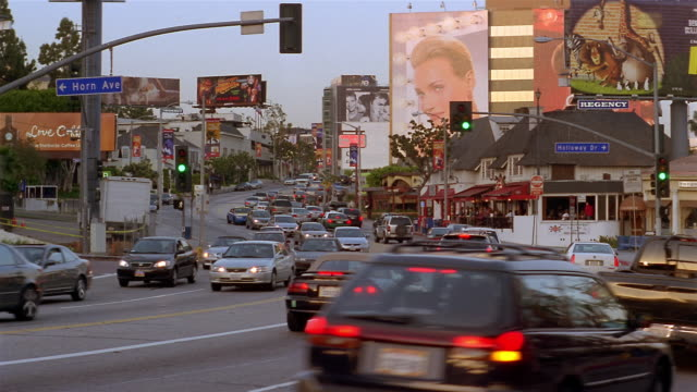 long shot traffic on sunset boulevard at sunset / los angeles - sunset boulevard stock-videos und b-roll-filmmaterial