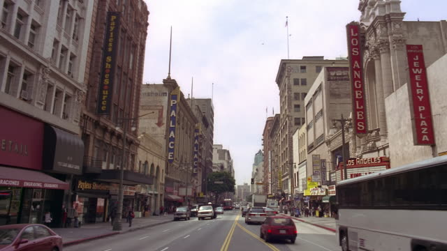 long shot traffic passing palace theatre and los angeles theatre on south broadway / los angeles - downtown stock videos & royalty-free footage