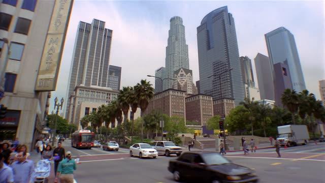 Long shot traffic passing street corner by Biltmore Hotel / view of US Bank Tower / Los Angeles