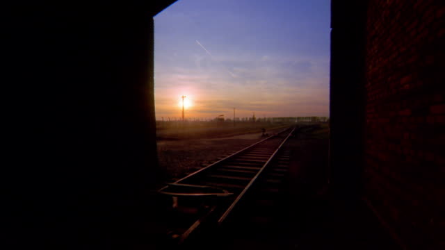 long shot train tracks and  tunnel at birkenau concentration camp w/sunset in background / auschwitz, poland - konzentrationslager stock-videos und b-roll-filmmaterial