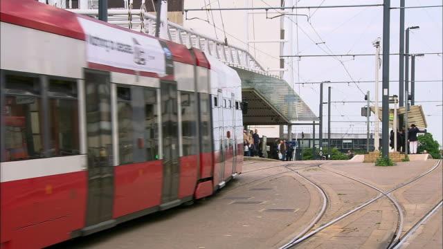 long shot tram pulling into east croydon station / london - ロンドン クロイドン点の映像素材/bロール