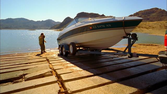 long shot truck backing motorboat into water at boat launch / man waving / phoenix, arizona - nautical vessel stock videos & royalty-free footage