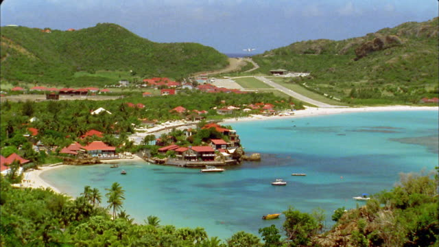 vidéos et rushes de long shot turquoise water in harbor with airplane taking off runway in background / st. barts - antilles occidentales