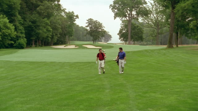long shot two men walking on golf course with golf bags and talking - golf shoe stock videos & royalty-free footage