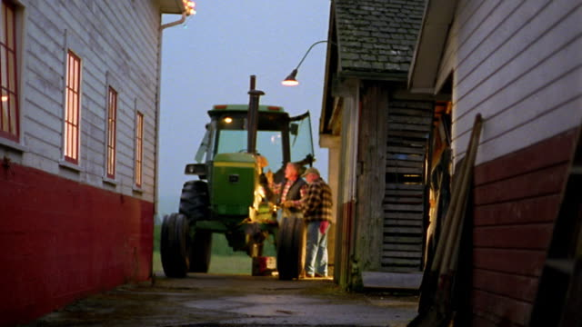 Long shot two men working on tractor under light from lamp on barn wall