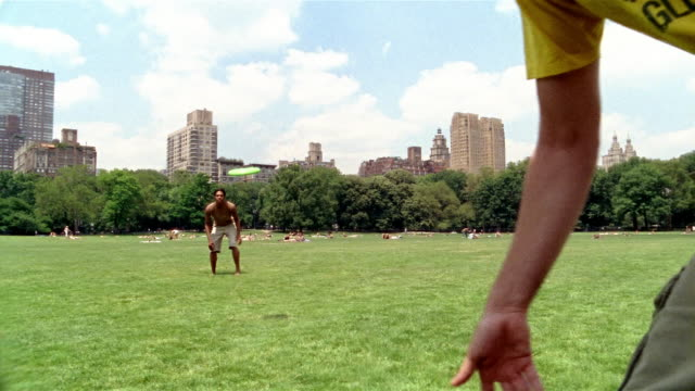 vídeos y material grabado en eventos de stock de long shot two young men playing frisbee in central park / new york city - tiempo real